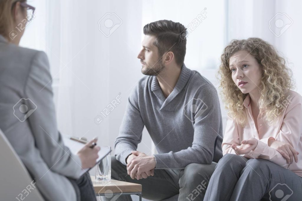 Young married couple talking to attorney after loss